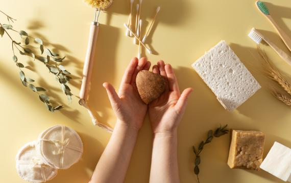 child's hands holding a heart shaped bar of organic soap surrounded by other sustainable products like a bamboo toothbrush and eco-friendly sponges