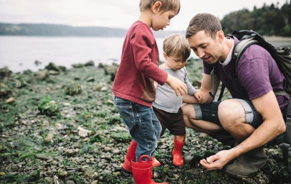 Dad and two little kids looking at rocky beach and tide pool finds