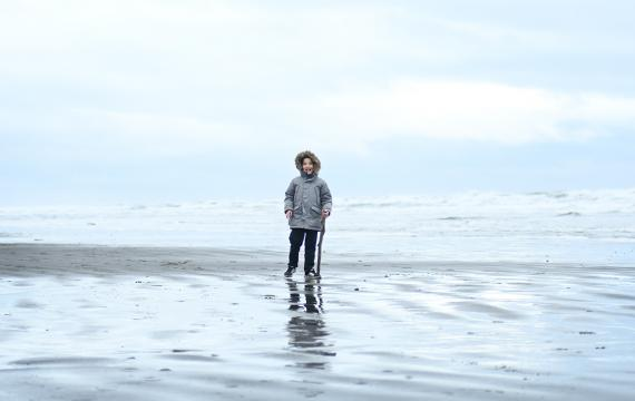 Boy in warm winter jacket standing on an empty Pacific ocean beach on an off-season getaway to the Olympic peninsula