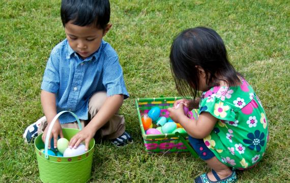 Two small kids brother and sister sitting in the grass and inspecting their Easter baskets full of plastic eggs