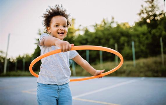 Happy young Black girl in shorts and a t-shirt holding an orange hula hoop at the playground Best weekend events Seattle kids families
