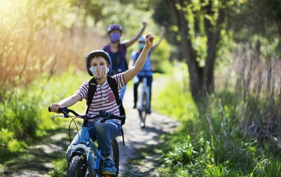 Family enjoying a spring bike ride, safely recreating by wearing masks