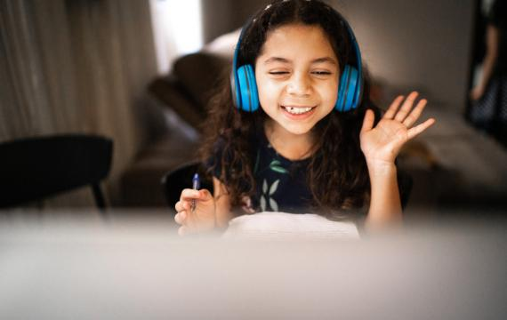 girl wearing headphones waving at her computer