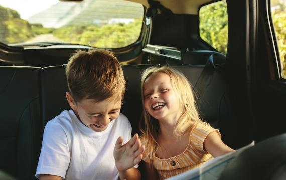 brother and sister giggling in the backseat of the car