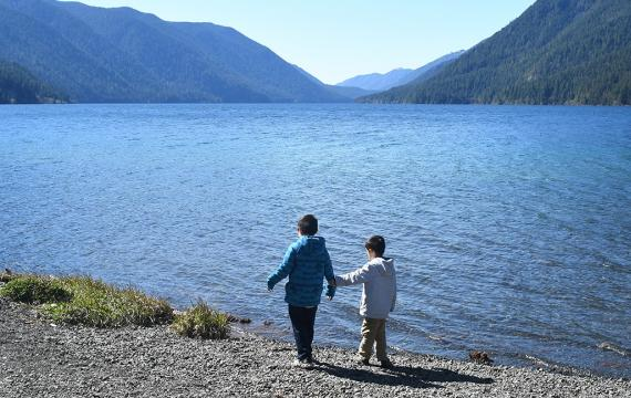 Brothers in jackets stand at the shore of Lake Crescent on Washington's Olympic Peninsula a getaway spot for Seattle-area families
