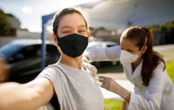 Teen girl taking a selfie while getting a vaccine