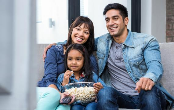 family sitting on a couch with popcorn and a remote