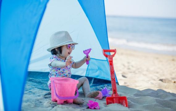 Kid-wearing-sunhat-sitting-in-tent-by-the-beach