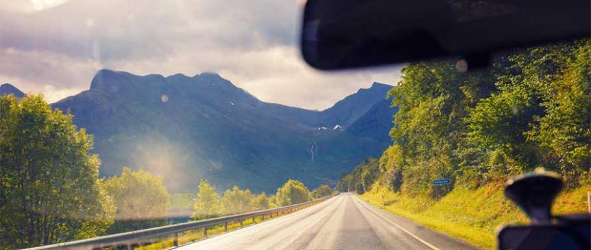 View out a car's windshield of open road, trees and mountains in the distance; best family road trips from Seattle