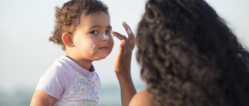 Mother applying sunscreen to her young daughter's face